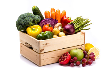 Pine box full of colorful fresh vegetables and fruits on a white background