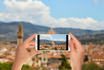 A tourist is taking a photo of Panorama of Florence on a summer sunny day with the Duomo of Santa Maria del Fiore in the center on a mobile phone