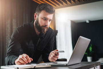 Bearded businessman is standing by computer, looking thoughtfully at laptop screen, holding pen, watching webinar.