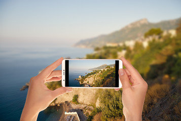 A tourist is taking a photo of landscape on the Amalfi Coast in Italy during the dawn on a mobile phone