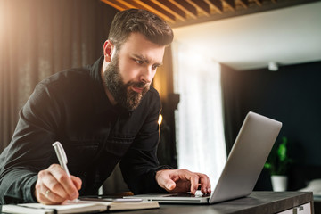 Businessman is standing by computer, looking at laptop screen, making notes in notebook. Man watching webinar, learning.