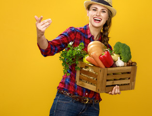 smiling woman grower with box of fresh vegetables beckoning