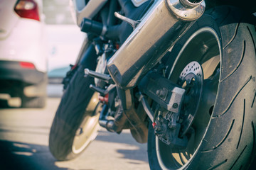 Rear view of the motorcycle. Rear wheel, exhaust pipe.