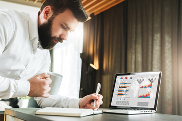 Bearded smiling businessman is standing by laptop, writing in notebook. Entrepreneur analyzes information, compares data
