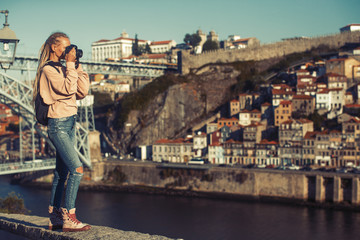 Girl taking pictures of Douro river, in the center of Porto, Portugal.