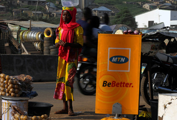 A woman stands near an MTN logo in Lokoja city