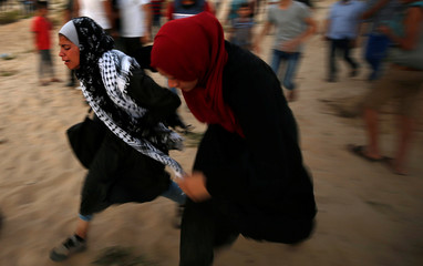 Palestinian women react to tear gas fired by Israeli troops during a protest calling for lifting the Israeli blockade on Gaza, near the maritime border with Israel, in the northern Gaza Strip