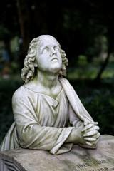 Grabstein mit betender Figur auf einem Friedhof in Frankfurt.