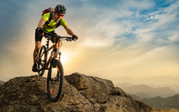 Cyclist Riding the Bike on Autumn Rocky Trail at Sunset. Extreme Sport and Enduro Biking Concept.