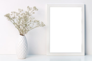 Desk with a white frame mockup with a vase with dried field flowers