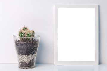 Desk with a white frame mockup with a glass flowerpot with a cactus
