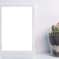 A real photo of desk with a white frame mockup with a glass flowerpot with a cactus