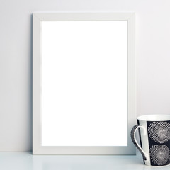 Desk with a white frame mockup with black and white mug