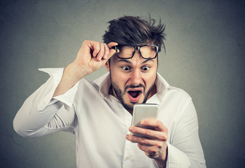 Shocked man reading news on smartphone