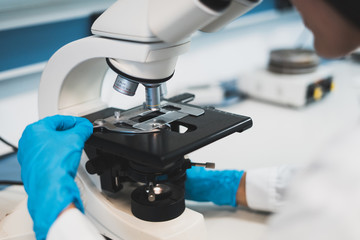 Person working with microscope in lab