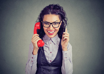 Cheerful woman with smartphone and retro telephone
