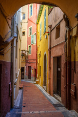 Path between colored houses in Menton, France