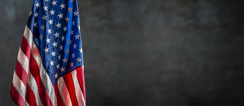 American flag freely hanging against a dark wall
