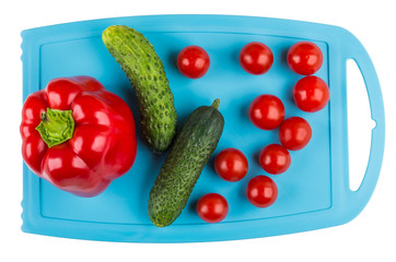 Sweet pepper, tomato, cucumbers on cutting board isolated on white