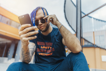 Young attractive man with blue dreadlocks looking at mobile phone screen.