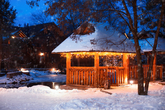 Beautiful gazebo decorated with bright garlands in winter