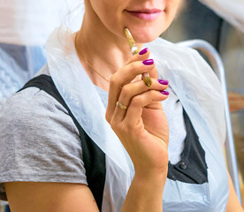 Smiling woman holding a paintbrush on an art masterclass in the studio