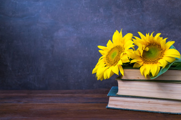 Vintage Old books and bouquet of sunflowers. Two books with bright yellow flowers. Retro nostalgic vintage background. Reading, learning, education, library concept mockup
