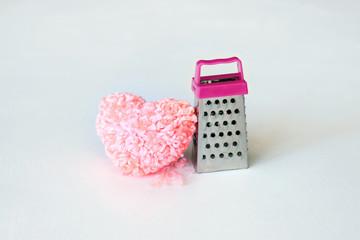 Pink fluffy heart and thread scraps at the grater. Hard breakup, Heartache cure, divorce, broken heart concept