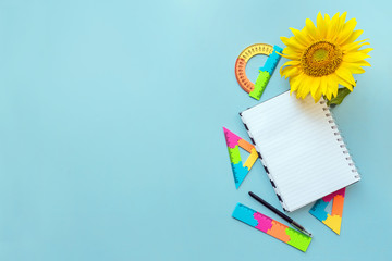 School open white notebook and sunflower on blue background, spiral notepad on a table. Still life, business, office, education concept, mock up