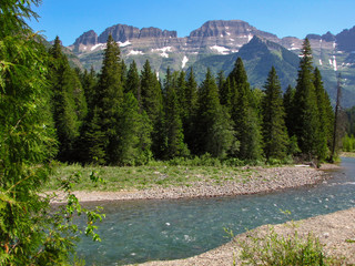 Beautiful nature landscape of a turquoise river, pine trees and mountains in Glacier National Park, Montana, USA