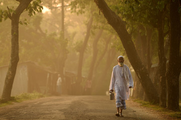 A man carries a food canister and torch at dawn along the road in Cox's Bazar