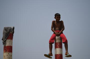 A boys sits atop a pillar in Cox's Bazar