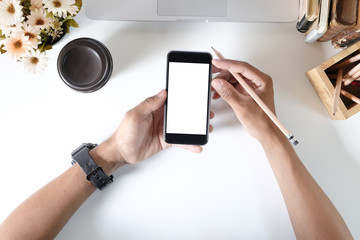 Man holding mockup smartphone on office desk.