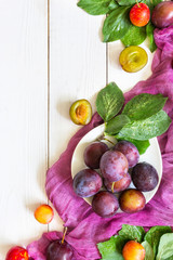 Eating fruit plum on a light wooden background flat lay top view of the layout