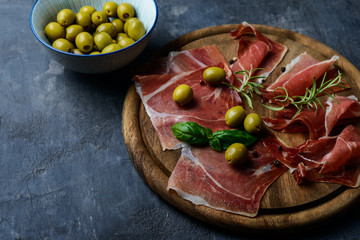 Meat plate, thin slices  of prosciutto or spanish jamon with olives on  cutting board