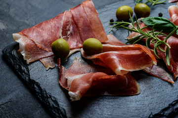 Meat plate, thin slices  of prosciutto or spanish jamon with olives on  cutting board, close up