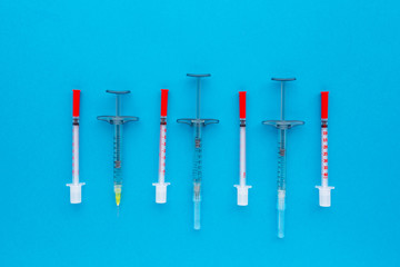 Syringes organized in a row over blue background, top view. Mock up health care medical background.