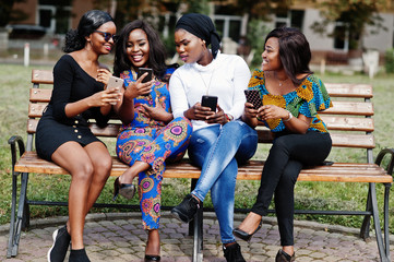 Group of four african american girls sitting on bench outdoor with mobile phones at hands.