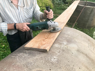 The man works with his hands, grinds the disk around for the grinder, the electric tool for grinding and polishing the surface of the wooden board