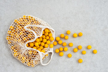 Lots of yellow plums in a mesh shopping bag