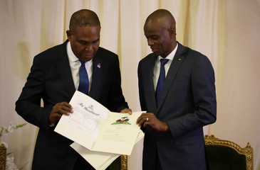 Haiti's PM Ceant checks documents beside President Moise during his inauguration ceremony at the National Palace in Port-au-Prince