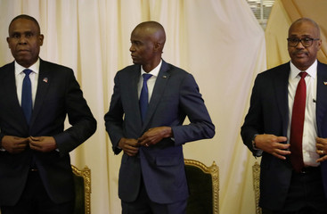 Haiti's PM Ceant, President Moise and former PM Lafontant button their jackets during the inauguration ceremony at the National Palace in Port-au-Prince