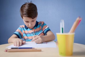 European boy carefully drawing with colorful pencils.