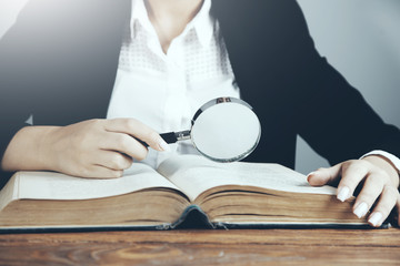 woman reading book with magnifier