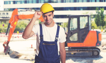 Red earthmover with handsome latin american construction worker