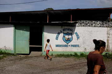 People walk in front of a school on the first day of class, in Caucagua