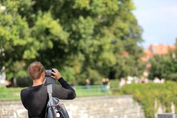 Mężczyzna z plecakiem robi zdjęcia telefonem komurkowym, smartfonem we Wrocławiu.