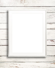 Blank white picture frame on white wood background.