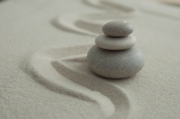 Foto op Plexiglas Stenen in het Zand Pyramids of gray zen stones on the sand with wave drawings. Concept of harmony, balance and meditation, spa, massage, relax