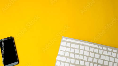 Wall mural Office desk table Top view with keyboard  with smartphone  yellow background